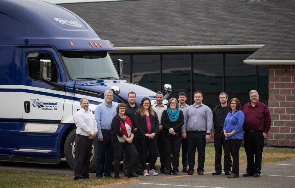 Professional Carriers' office team in front of truck